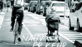 Old woman using electric wheel chair in a bike path surrounded by a biker and a lot of cars in the streets of Madrid